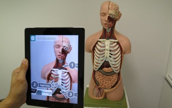 Photo of person using device to view a real-world object with AR