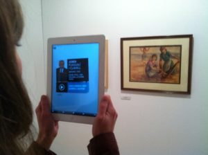 Photo depicting a person using their iPad's camera to view extra information about a painting in front of them.