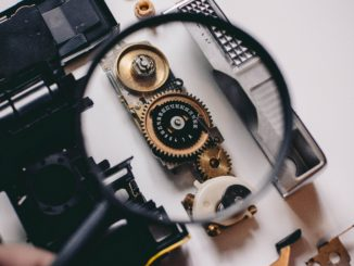 Magnifying glass focusing on cogs of disassembled echanism