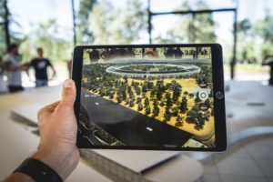 Person holding an iPad looking at an augmented design model