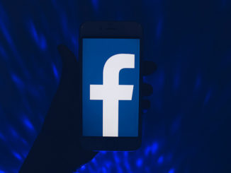 In a dark room swirling with dark blue light, a hand holds a smartphone displaying the Facebook logo
